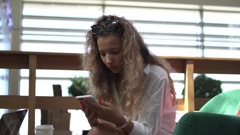 Curly haired lady in white surfs social nets on smartphone ライブ動画