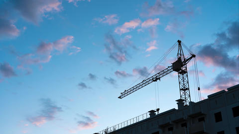 Tower crane against the sky. At dusk, clouds move across the blue sky. Concept Live Action