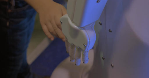 Close up view of boy hand holds white plastic hand of humanoid robot in Robotics Footage