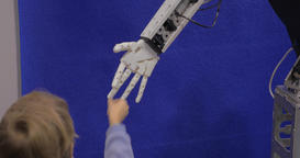 Close up view of boy hand holds white moving plastic hand of humanoid robot in R Footage