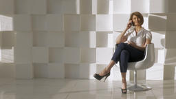 In studio a young girl sitting in a chair and talking on a mobile phone Footage