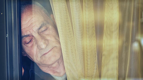 Sad old and tired man looks what happens outside the window Footage