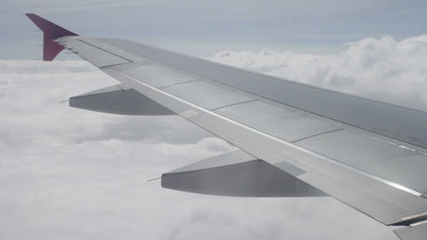 Wing of airplane flying above the clouds in sky Archivo