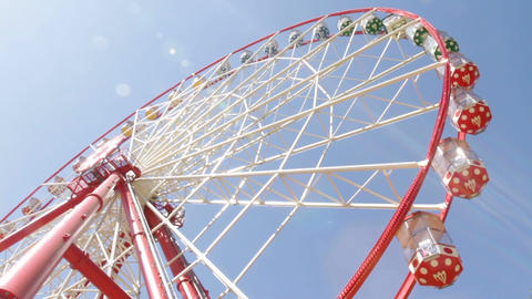 Brightly colored ferris wheel against the blue sky Footage