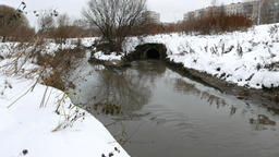 Storm drain outlet pipe, dirty stream join with runlet, snowy ground banks Footage