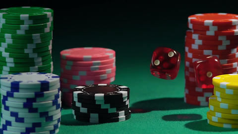 Red dice falling upon stacks of poker chips in slow motion, casino background Footage