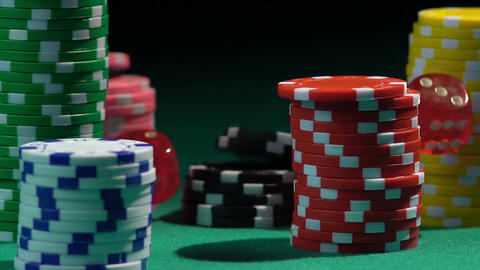 Stacks of colored poker chips on green casino table, red dice falling from above Footage