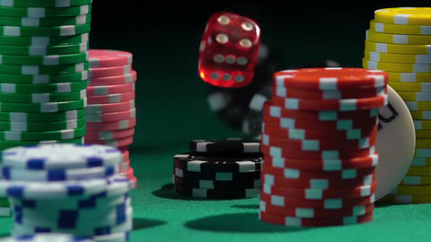 A large number of chips lying on green gambling table, throwing dice in slow-mo Footage