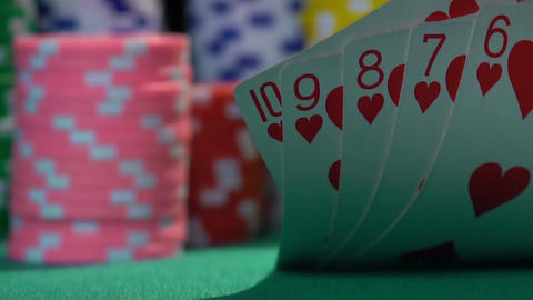 Winning combination, straight flush. Successful poker player checking his hand Live Action