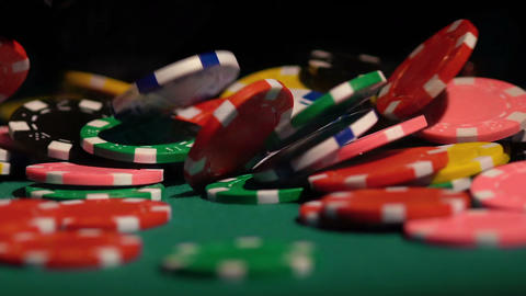 Winning jackpot in casino, many poker chips falling on green table in slowmotion Footage