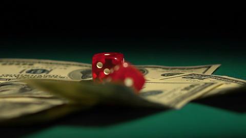 Red dice falling on money, gambler playing game at casino, addiction to gambling Footage