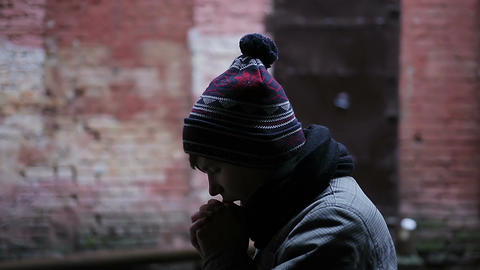 Miserable young man putting on hat, teenager blowing to warm up cold hands Footage