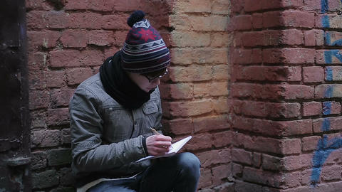 Romantic young man sitting alone in deserted place, writing poetry in notepad Footage