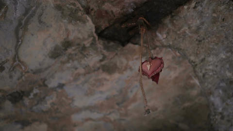 Old heart shaped fabric decoration hanging on stone ceiling, heartbreak, breakup Live Action