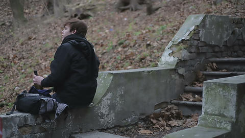 Back view of lonely young man drinking alcohol on old demolished stairs in park Footage