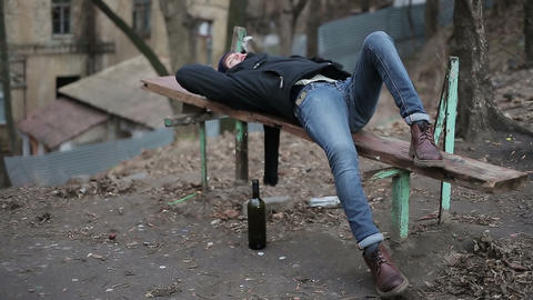 Drunk young guy lying on bench, alcohol abuse problem, hangover after party Footage