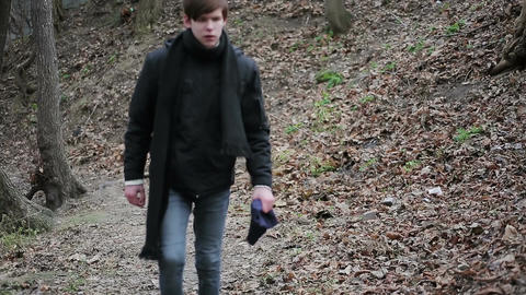 Aggressive young man walking alone in forest, annoyed with life, disappointment Footage