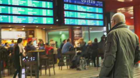 Cafeteria in the waiting room, old man with eyeglasses looking at train schedule Live Action