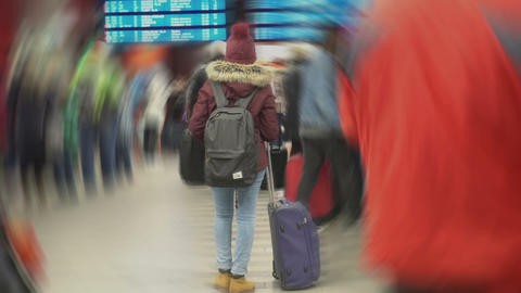 Female student waiting for her airplane, looking on schedule. Creative effect Footage