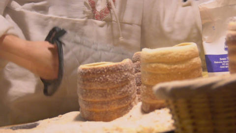 Street seller putting tasty pastry in small basket, food festival, European food Footage