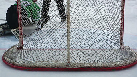 View from behind net, hockey goaltender repulsing violent attack, catching puck Footage