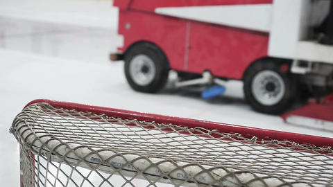 Close-up of hockey net, ice resurfacer driving rink to make surface smooth Footage