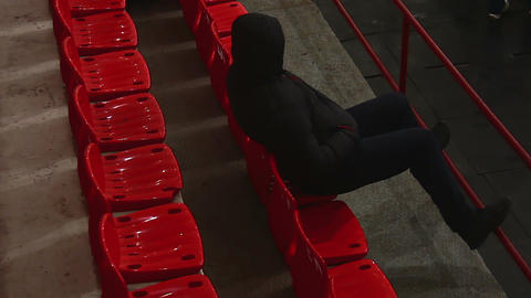 Strange man in black clothes sitting on tribune, looking around suspiciously Footage