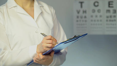 Female ophthalmologist examines patient, writes down diagnosis and treatment Footage
