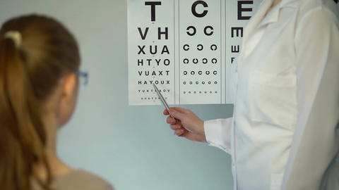 Eye examination, girl puts on glasses to check eyesight at the ophthalmologist Footage