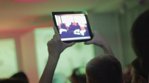 Concert in the nightclub, people dancing, man filming popular band with tablet Footage