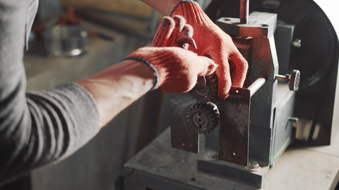 Close-up of a locksmith working with a metalworking machine repairing a machine Live Action