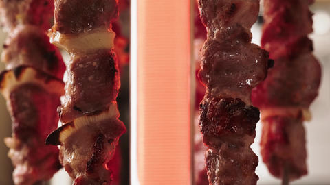 Pieces of meat dressed in skewers rotate during cooking. Cooking meat Live Action