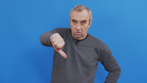 Sad man in basic casual blue t-shirt isolated on blue background studio. People Live Action
