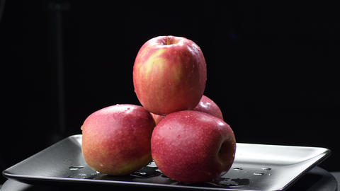 Apples fruit in a black tray gyrating on black background Live Action