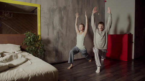 A guy and a girl do morning yoga exercises together in the morning. Greeting to Live Action