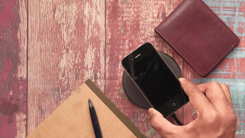 charging Smartphone Using Wireless Charging Pad, top view Live Action