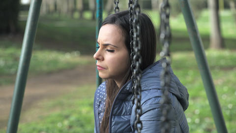 sad and distressed girl on the swing in a city park Footage