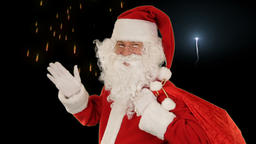 Santa Claus carrying his bag, looks at the camera sends a kis and wave, firework Animation