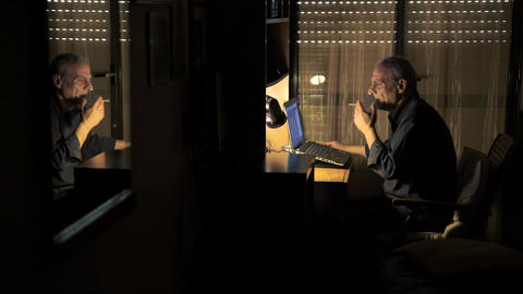 elder man chatting with the computer in his room's twilight Footage