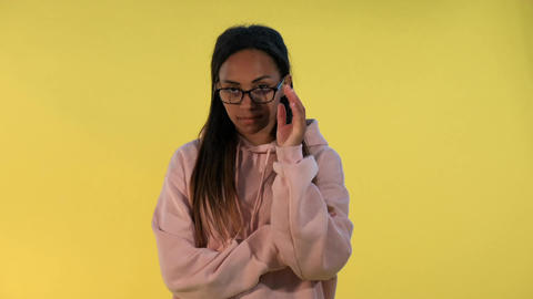 Multiethnic young woman looking over her glasses on yellow background Live Action