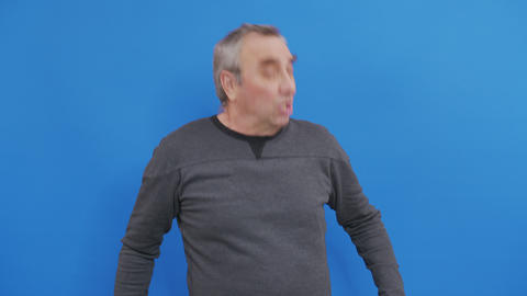 Sick man sneezing in studio. Close up ill men sneezing on blue background Live Action
