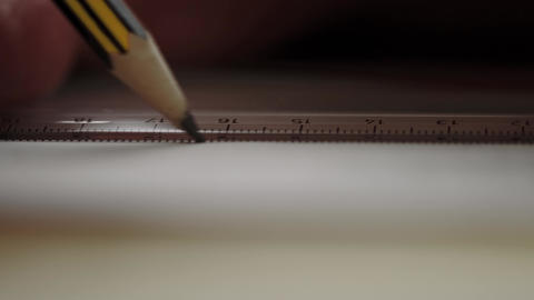 A slate pencil draws a line along a ruler on a white piece of paper. Drawing or sketching Live Action