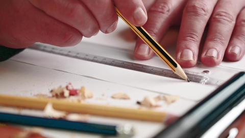 male hand with a slate pencil drawing lines along a ruler on a white sheet of paper Live Action