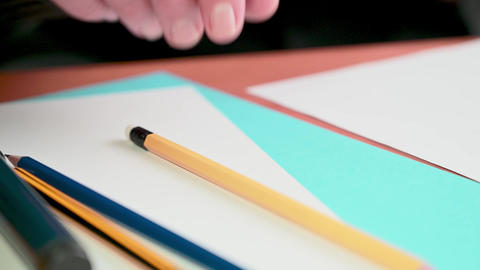 Close-up of a man's hand takes a slate pencil and knocks it on the table in thought Live Action