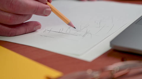 Male hand draws with slate pencil on a white sheet of paper. Drawing or sketching Live Action