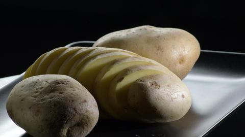 Potato cut gyrating on a black tray on black background. Solanum tuberosum Live Action