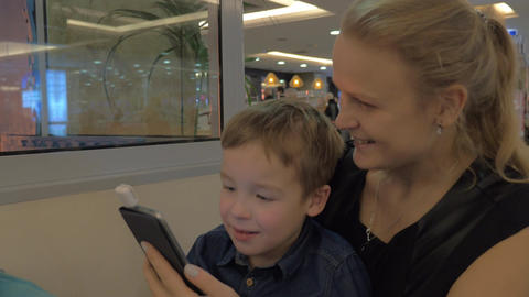 Mother and son paying with mobile card reader Footage