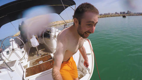Young man filming himself jumping in the water from a boat Live Action