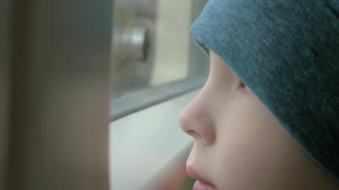 In train rides a little boy in a cap who looks out the window Footage