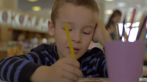 At the table sitting a little boy and draws with colored pencils Footage